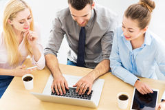 Business people using laptop together Royalty Free Stock Photography