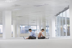 Business People Using Laptops In Empty Office Space Royalty Free Stock Image