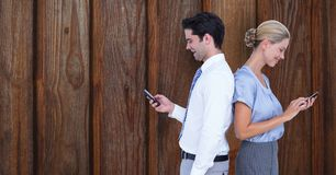 Business people using smart phones against wooden wall Stock Photography