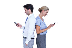 Business people using smartphone back to back Stock Photography