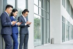Business people using smartphones. Group of Asian business people in formal wear using mobile phones together while standing near the office building outdoors stock photography