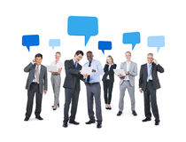 Business People Using Technological Devices. Group of Business People Using Technological Devices with Blank Speech Bubbles Above Them Stock Photography