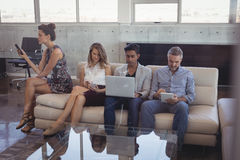 Business people using technologies at creative office. Business people using technologies while sitting on sofa at creative office Stock Photos