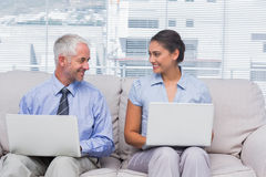 Business people using their laptops and smiling at each other Royalty Free Stock Photos