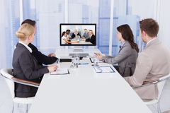 Business people in video conference at table Stock Photos