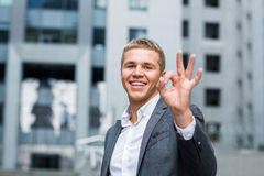 Business, people, vision and success concept - happy smiling businessman in eyeglasses and suit showing ok sign over office buildi Stock Photo