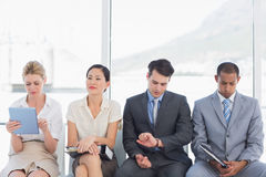 Business people waiting for job interview. Four business people waiting for job interview in a bright office Stock Photo