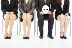 Business people waiting for job interview with a strange mask. On a chair Stock Photography