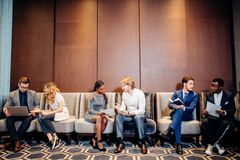 Business people waiting for job interview, talking. And smiling Royalty Free Stock Image