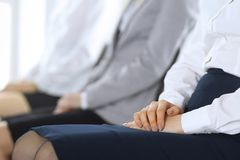 Business people waiting for job interviews or taking part at conference in office, close-up. Women sitting on chairs stock images