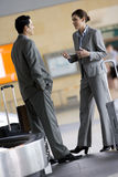 Business people waiting for luggage in baggage claim Royalty Free Stock Image