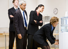 Business people waiting turn at water cooler Stock Images