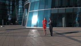 Business people walk in glass financial district. Slow motion: business people walk talking near glass financial building. Woman - boss, man - employer. Digital stock footage