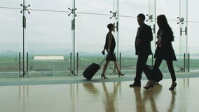 Business people walking in airport terminal. Asian business man and woman in formal wear walking and talking in airport terminal building stock footage