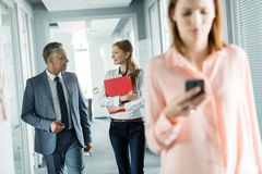 Business people walking in corridor with female colleague using mobile phone in foreground at office Royalty Free Stock Photography