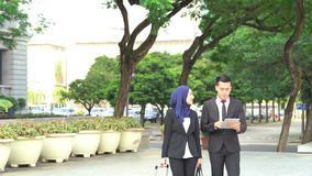 Business travel concept. Business people walking and discussing, using tablet pc outdoor stock video footage