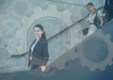 Business people walking down stairs with gear graphics overlay. Digital composite of Business people walking down stairs with gear graphics overlay Royalty Free Stock Image