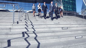 Business people walking down stairs stock video