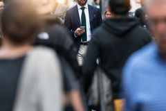 Business people walking from the job in busy city street. Elegant businessman in the people crowd walking and texting on the phone Stock Image