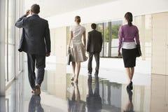 Business People Walking On Marble Flooring. Full length rear view of business people walking on marble flooring in office Royalty Free Stock Photos