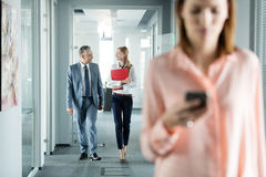 Business people walking in office corridor with female colleague using mobile phone in foreground Royalty Free Stock Photos