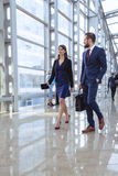 Business people walking in office corridor. Business people walking in modern glass office corridor Royalty Free Stock Images