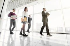 Business people walking in the office corridor. Walk team. stock photos