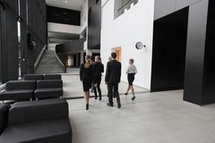 Business people walking in office lobby. And talking Royalty Free Stock Image