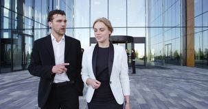 Business people walking outdoors. Two business people walking outdoors office building stock video