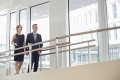 Business people walking by railing in office Royalty Free Stock Images