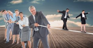 Business people walking on rope while colleagues pulling it on boardwalk stock image
