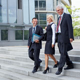 Business people walking together. Three happy business people walking together outside Royalty Free Stock Image