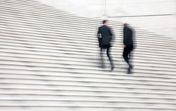 Business people. Walking up the stairs of office building while discussing royalty free stock photography