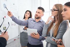 Business people watching infographics at flip chart. In office stock images