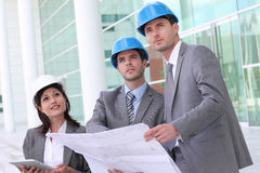 Business people wearing helmets with blueprint Royalty Free Stock Photo