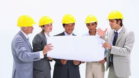 Business people wearing helmets are looking at blueprints Royalty Free Stock Photography