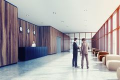 Wooden office meeting room and reception, people. Business people in a wooden office lobby with a concrete floor, panoramic windows, a black wooden reception Stock Photo