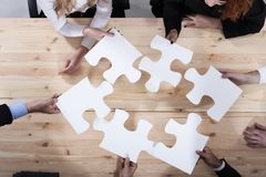 Business people work together to build a puzzle. Concept of teamwork, partnership, integration and startup. Business people work together in office to build a stock photos