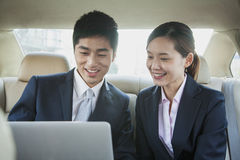 Business People Working in Back Seat of Car Stock Image