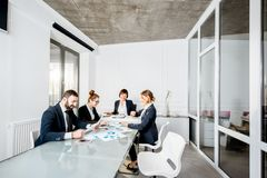 Business people during the conference in the office. Business people working with charts and documents sitting at the table during the conference in the office royalty free stock photo