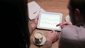 Business people working with charts on tablet. Business people working with documents and tablet in cafe stock footage
