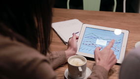 Business people working with charts on tablet. Business people working with documents and tablet in cafe stock video