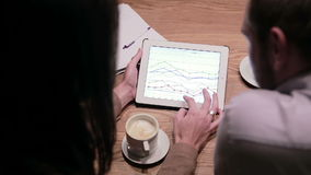 Business people working with charts on tablet. Business people working with documents and tablet in cafe stock video footage