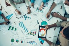 Business People Working with Diagrams in Office. Group of Colleagues Sitting at Desk and Working Together on Charts and Diagrams. Comunication between stock photos