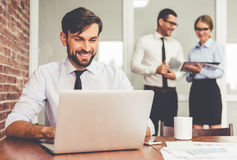 Business people working. Handsome businessman is using a laptop and smiling while working in office, his colleagues are studying documents in the background stock photo