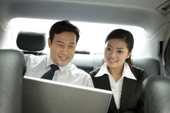Business people working with laptop in the car Royalty Free Stock Image