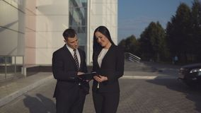 Business people while working near office building. Business meeting. Young beautiful businesswoman talks and shows documents to young male employee outdoors stock footage