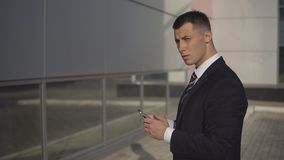 Business people while working near office building. Side view - young handsome manager of large company typing text on smartphone standing on background of stock video