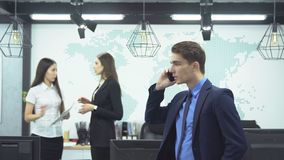 Business people working in office. Business concept. Young businessman in suit talking on the phone on background of two young female employees discussing work stock footage