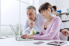 Business people working at office desk. A women is using a laptop and her chief is watching the computer screen Stock Photos